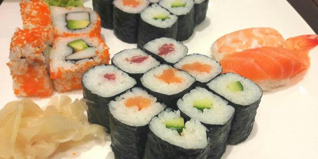 Sushi platter containing uramaki, hosomaki, nigiri and California roll with picked ginger and wasabi