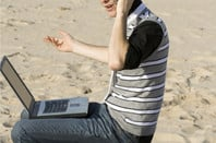 Man sits on sand with laptop