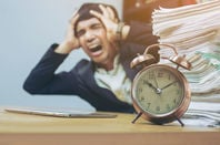 Business: Stressed man with pile of paperwork works against the clock