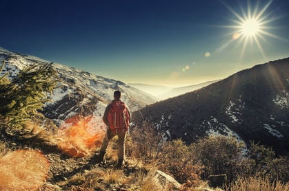 a hiker pauses on top of the sierra nevada mountains