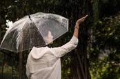 rainy day - woman with umbrella checks to see it is still raining