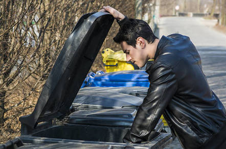 man in leather jacket rummages through bin