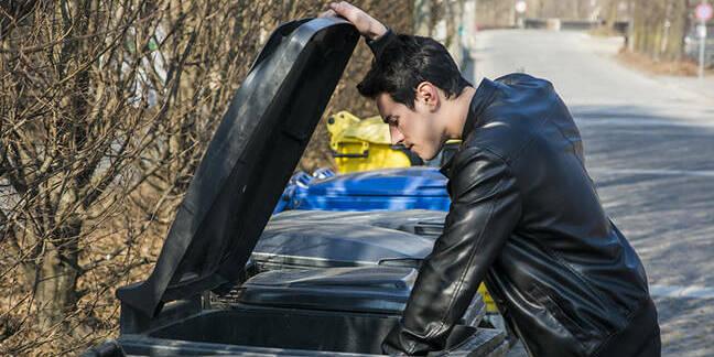 man in leather jacket rummages through bin