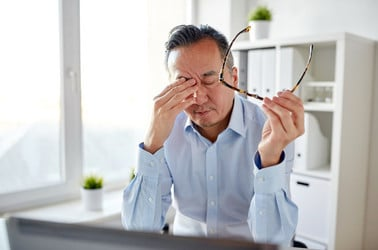 Tired IT worker rubs his eyes
