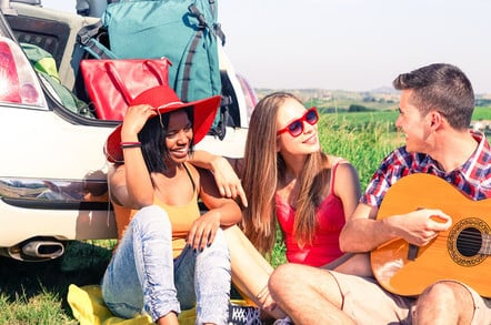 youngsters going to a music festival - man plays guitar, boot packed with luggage