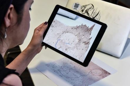 Layla Gordon pointing tablet at 2D map of Mars to generate 3D image