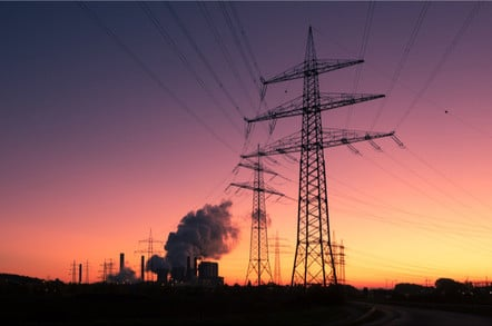 Power plant + electricity pylons at sunset