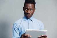 Man looks put off by something he's seen on a tablet