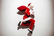 Man dressed as Santa claus runs away with loot in a bag.