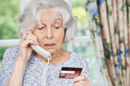 Older woman on phone gives credit card number.