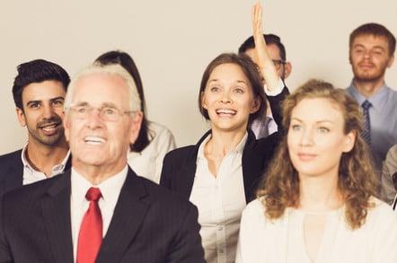 Businesswoman enthusiastically volunteers, raises hand