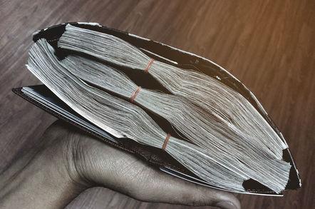 Wallet stuffed full of bundles of cash