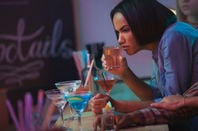 Woman pulls face while tasting dubious cocktail.