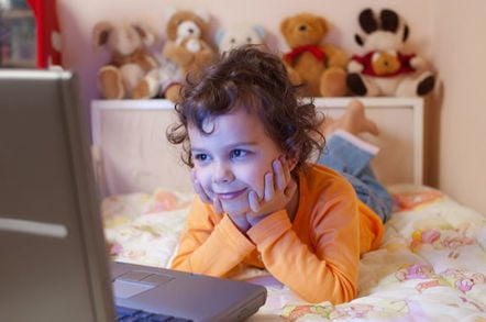 Child surrounded by stuffed animals watches video on computer