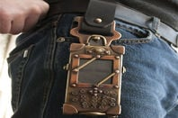 Belt with antique looking cellphone strapped to it in a brass pouch