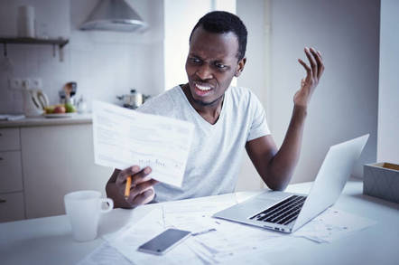 upset man looks at paper in front of laptop