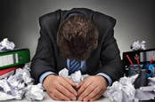 Man bows head amongst piles of crumpled paper