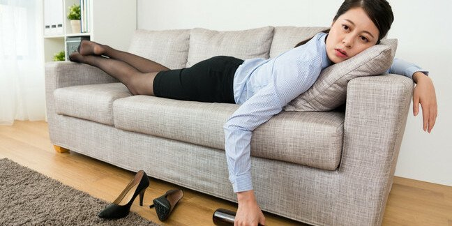 Woman kicks off shoes, gets bottle of wine, collapses onto couch