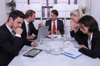 Office workers in meeting seem frustrated.