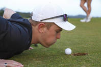 golfer tries to blow ball into hole