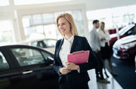 Car sales person walks away, smiling brightly, from couple looking at car...