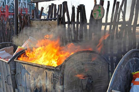 Dumpster fire against background of wooden fence with sad green recycling badged nailed to it
