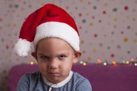 A sad child in a holiday hat