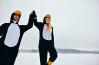 Couple dressed as penguins celebrate in the snow