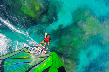 smug windsailing man on turquoise ocean makes surfer sign at gopro camera