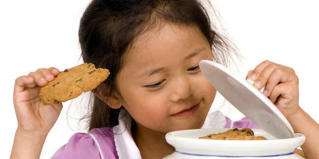 little girl takes cookie/biscuit out of large ceramic jar