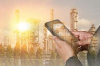 Man holds mobile phone against backdrop of factory/industrial plant
