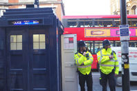 Met police coppers in high vis yellow vests in front of a police box