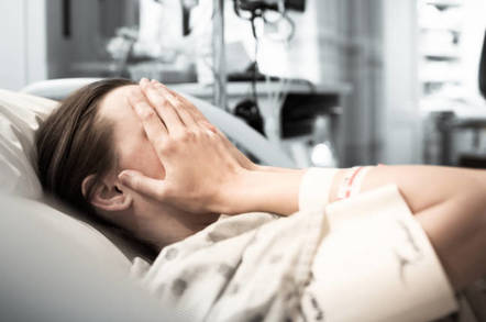 Woman in hospital (in hospital gown) covers face with hands