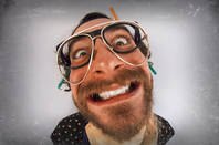 Bearded man with crazed expression wearing multiple pairs of glasses