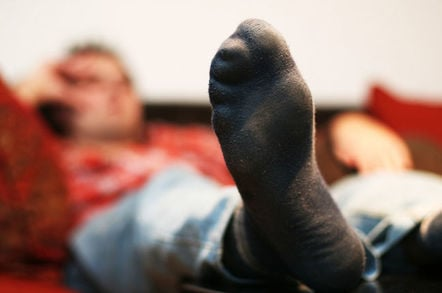 man relaxes on couch in socks