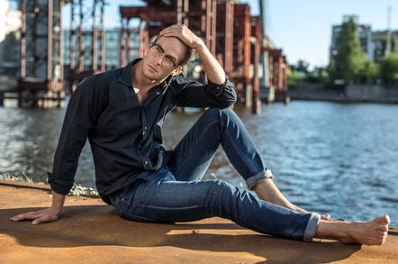 Tall, slim male model poses by canal