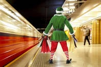 an elf with his back t the camera waits for a subway train