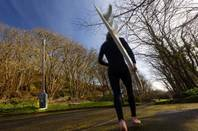 "Cornwall: A barefoot surfer in a wetsuit walks past a clump of bushes with a 8-metre high ""telescopic"" 4G mast in the middle."
