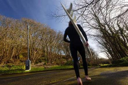 """Cornwall: A barefoot surfer in a wetsuit walks past a clump of bushes with a 8-metre high """"telescopic"""" 4G mast in the middle."""