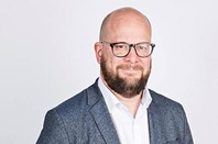 London's new chief digital officer, Theo Blackwell. Smiling bearded man in a tailored but loose mixed material jacket over jeans and a brown belt