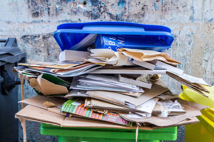 paper and cardboard stuffed into an overfull recycling bin