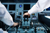 Two pilots operating on the controls of a commercial jet aircraft