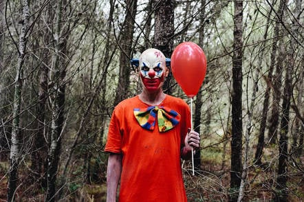 Creepy clown holding balloon in woods