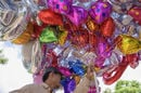helium balloons - massive bunch held by man selling them