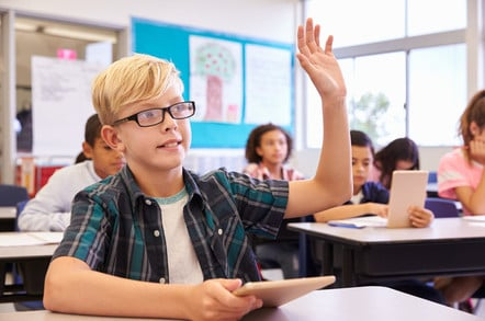 Nerdy kid in class with hand up