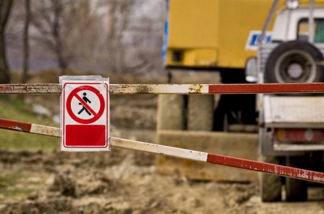 Boom across construction area with sign denying walkers access