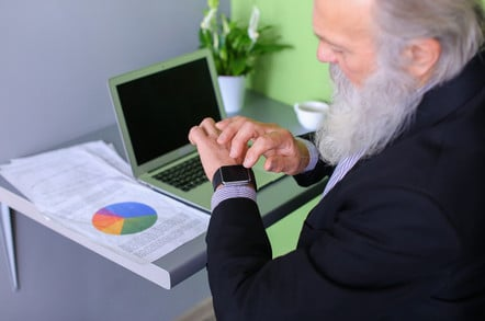 Older bearded man inputs data from a printed chart into a computer