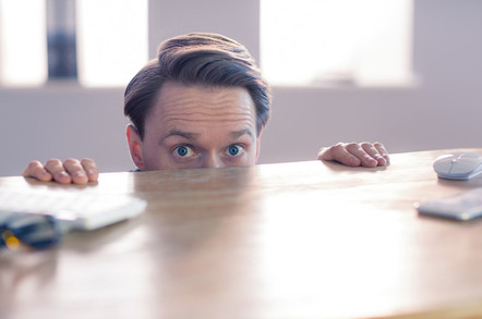 Scared looking office consultant hides under desk