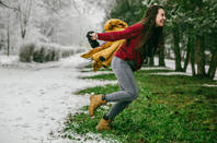 Woman leaping from winter to spring