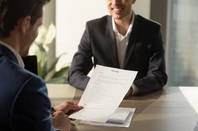 Employer looks at smiling candidate's CV